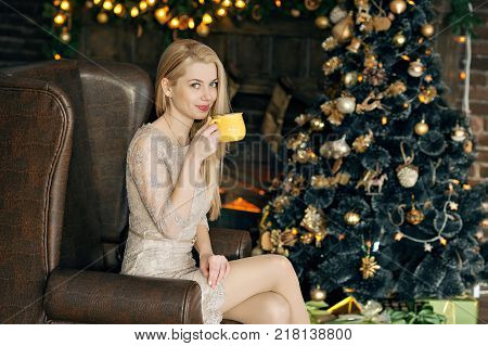 Young woman in a cozy interior of Christmas. A girl is sitting with a yellow mug under a Christmas tree among many presents. Preparing for Christmas. The concept of a holiday.