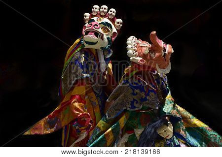 Tibetan monks in carnival costumes perform the ancient sacred dance Mask in ritual bright clothes.