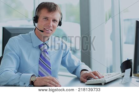Happy young man working at callcenter, using headset