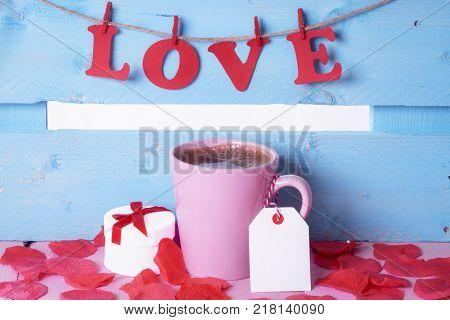 Coffee cup with a gift and the word love - Pink cup of coffee with a label attached to its handle near a gift surrounded by soap rose petals and the word love written with red paper letters.