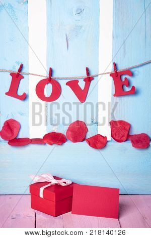 Message card near gift and word love - Cute red gift box with a blank message card near it and the word love written in red paper letters tied to a string on a blue wooden fence.