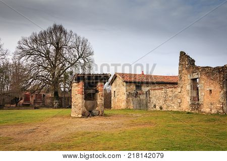 ORADOUR SUR GLANE FRANCE - December 03 2017 : in the middle of the ruins of the village destroyed by fire during the massacre of polulation by the Nazis on June 10 1944 a small water well remained intact.