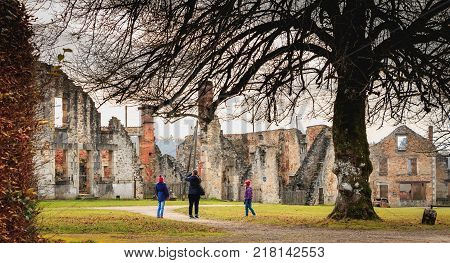 ORADOUR SUR GLANE FRANCE - December 03 2017 : tourists visit and take pictures of ruins of houses destroyed by fire during the massacre of the population by the Nazis on June 10 1944
