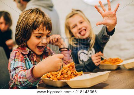 Happy children having fun while eating spaghetti pasta in fast food restaurant