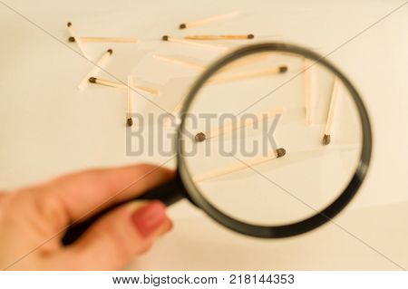 Match sticks with brown heads in a row. Matches under magnifier, white background.