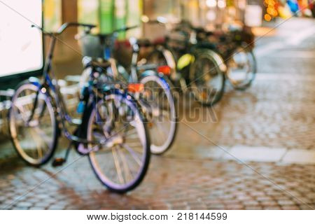 Row Of City Parked Bicycles Bikes In European City In Night Time. Natural Defocused Boke Bokeh Background Effect. Design Backdrop.
