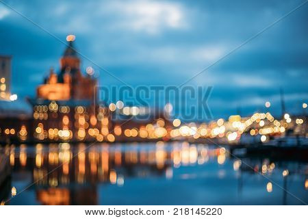 Helsinki, Finland. Abstract Blurred Bokeh Architectural Urban Background Of Uspenski Cathedral And City Embankment. Real Defocused Colorful Backdrop Lights Of City Street In Evening Night Illumination