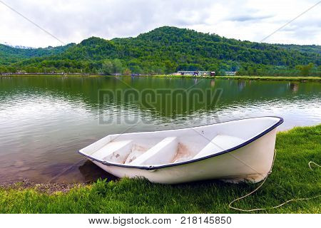 A boat without oars tied with a rope is on the green grass in front of the pond on the background of the countryside and the forest mountain landscape. White boat on the lake shore, Sochi, Russia.