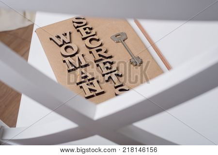 The book is wrapped in old paper and signed with wooden letters woman secrets, on the book key. White background chair in the interior of the house.