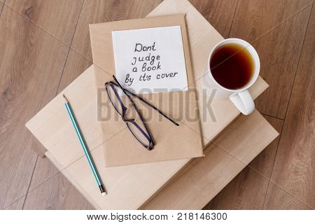 Dont judge a book by its cover - a handwritten inscription on a napkin. Background book in the old cover, on a chair in the interior of the home.