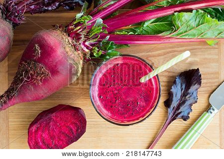 Red beet juice in a glass with red beets in the background top view