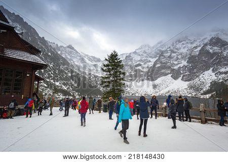 ZAKOPANE, POLAND - NOVEMBER 11, 2017: Tourist at Morskie Oko lake (Eye of the Sea) in Tatra mountains, Poland. Morskie Oko located in the Tatra National Park is popular tourist destination in Poland.
