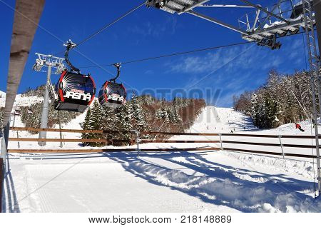 Jasna Slovakia - December 1 2017: View of the ski slopes and cabins of the cableway at the station on the south side of Mount Chopok on a sunny day in the ski resort Jasna Low Tatras Slovakia.