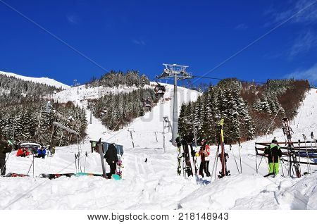 Jasna Slovakia - December 1 2017: Skiers cableway and snow slopes on the south side of Mount Chopok on a sunny day in the ski resort Jasna Low Tatras Slovakia.