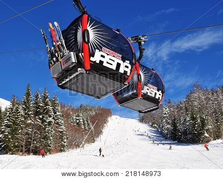 Jasna Slovakia - December 01 2017: Two cabs of the cableway and skiers on the ski of the mountain Chopok south side on a sunny day in the ski resort of Jasna Low Tatras Slovakia.