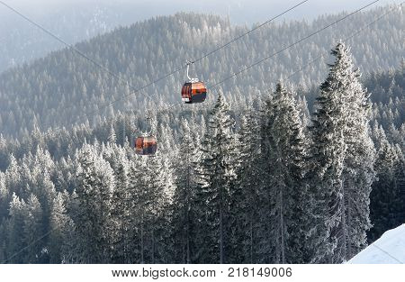 Jasna Slovakia - January 25 2017: View of two orange cabins cableway and snow-covered spruce trees in a winter forest in the ski resort of Jasna Low Tatras Slovakia.