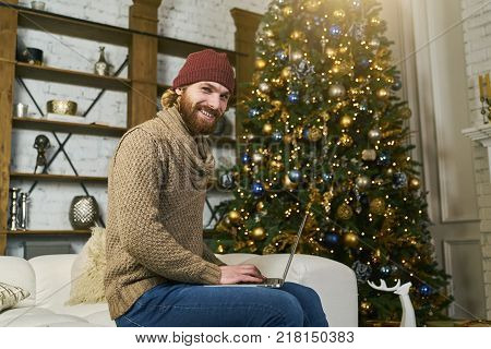 unrecognizable model using laptop at home during christmas. Buying online new year gifts. Christmas tree blur on background. Cozy apartmen decorated lights and deer