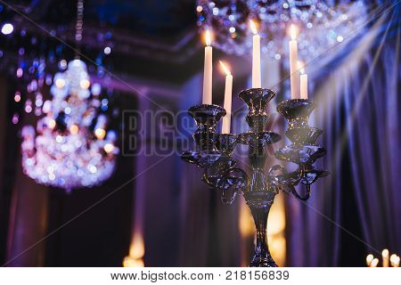 Interior shot of chic glowing candlestick in dark with shining crystal chandelier in luxurious hall.