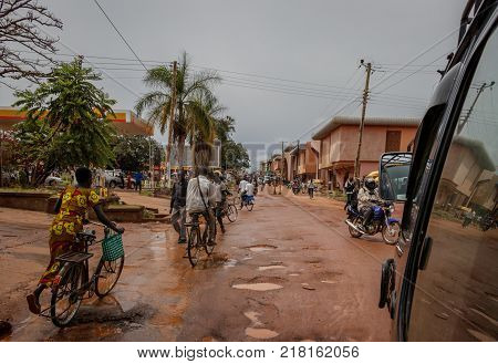 LIRA, UGANDA - NOVEMBER 04, 2017: Typical street life in Lira Uganda after a heavy rain shower. Many bicycles and a few cars trying to avoid the mud pools in the potholes in a easy going African town