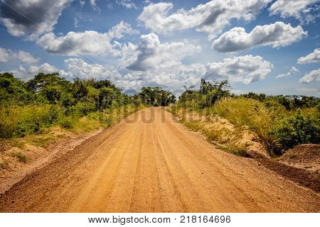 Very typical dirt road with a beautiful sky used for safari in Murchison Falls national park in Uganda. Oil drilling will soon take place in the nearby lake Albert.