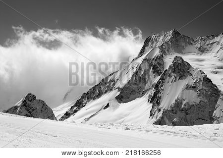 Black and white view on snowy sunlight mountains in clouds. Caucasus Mountains. Region Dombay in winter.