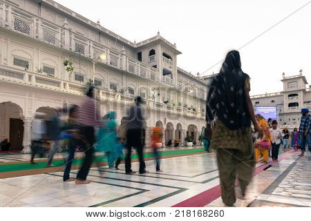 AMRITSAR INDIA - MARCH 20 2016: Horizontal picture of Indian sikh people on movement at Sri Harmandir Sahib known as Golden Temple located in Amritsar Punjab India.