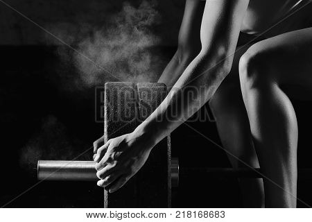Vertical shot of a female athlete preparing barbell for weightlifting at the gym magnesia protection powerlifting fitness strength athletics workout preparation focusng concentration
