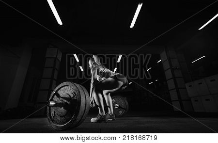 Rearview shot of a fitness woman with perfectly shaped toned strong body weightlifting at the gym bodybuilder bodybuilding confidence power strengthening heavy barbell equipment crossfit