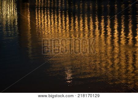 Reflection of night lights, bright yellow stripes of color on black water.