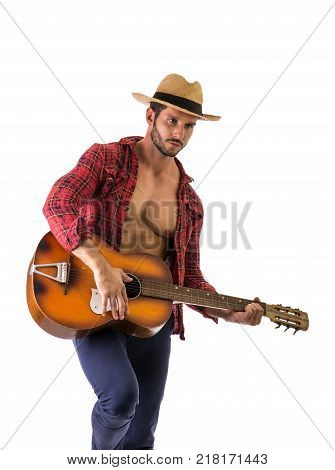 Studio portrait of handsome bearded man with unbuttoned shirt playing guitar over white background. Isolate.