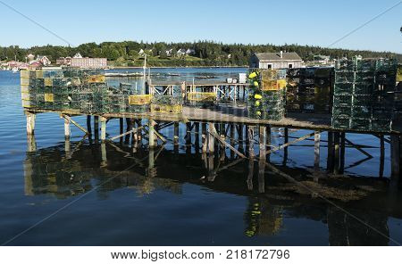 A dock over the blue water of Bass Harbor Maine has many lobster traps sitting on it ready to be planted in the water as the lobsters come in from the atlantic ocean in August.
