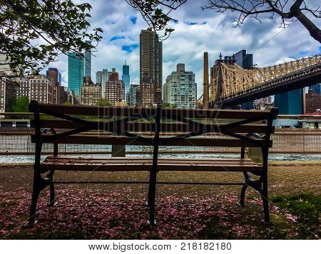 Bench at Roosevelt island, Queensboro bridge and Manhattan in colorful vintage