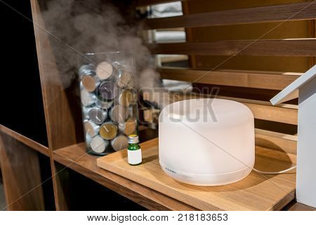 Electric aroma oil diffuser on wooden floor with green glass bottle
