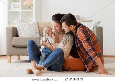 family, parenthood and people concept - happy mother, father with baby at home