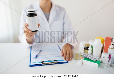 medicine, healthcare and people concept - doctor with drugs and clipboard showing jar with medication