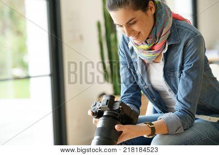 Photographer checking photo shots on camera screen