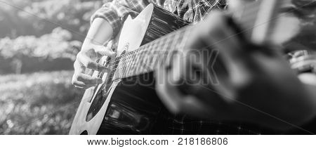 Female fingers playing guitar outdoor in summer park. Musician woman and her guitar in nature park Practice guitar. black and white. banner panoramic crop for copy space.
