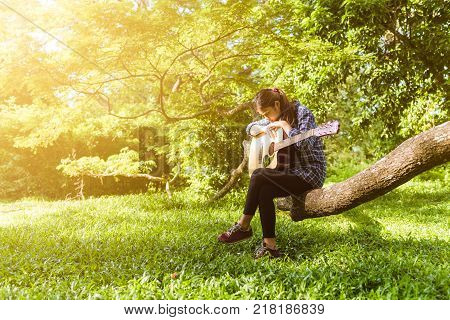 Female fingers playing guitar outdoor in summer park. Musician woman and her guitar in nature park Practice guitar.