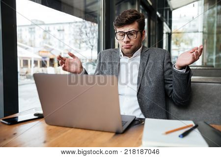 Confused business man in eyeglasses sitting by the table in cafe while shrugs his shoulders and looking at laptop computer