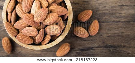 Almonds in brown bowl on textured wooden background top view. banner panoramic crop for copy space. Almond vintage tone. Close up almond background.  Close up view of almonds for texture.