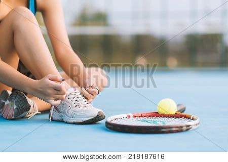 Tennis player tying shoelaces in court.  tennis ball on sunset. tennis sport girl. tennis ball and racket. tennis player vintage tone.