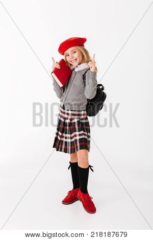 Full length portrait of a cheerful little schoolgirl dressed in uniform with backpack holding book and pointing fingers up at copy space isolated over white background
