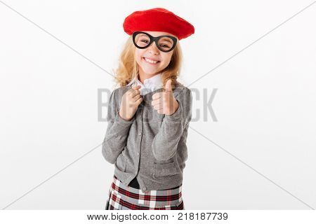 Portrait of a happy little schoolgirl dressed in uniform grimacing and showing thumbs up gesture isolated over white background