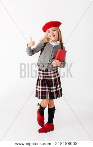 Full length portrait of a cheery little schoolgirl dressed in uniform with backpack holding book and showing thumbs up isolated over white background
