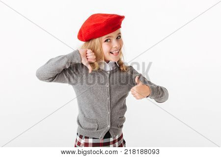 Portrait of a funny little schoolgirl dressed in uniform showing thumbs up and thumbs down isolated over white background