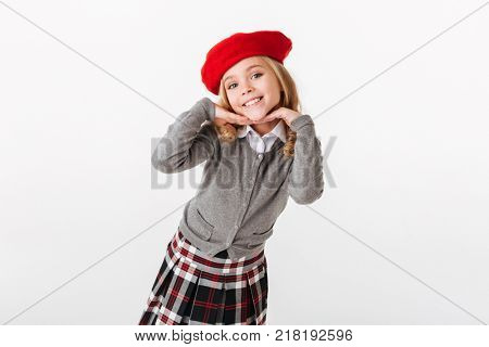 Portrait of a smiling little schoolgirl dressed in uniform posing and looking at camera isolated over white background