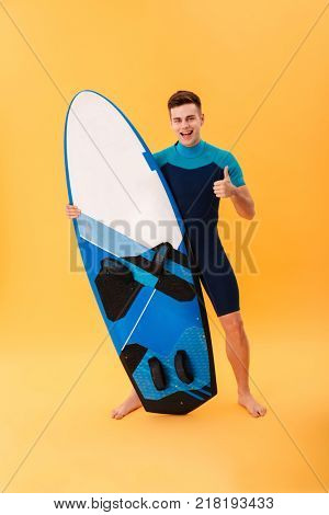 Full length portrait of happy handsome surfer showing thumb up gesture while standing and holding surfboard, isolated over yellow background