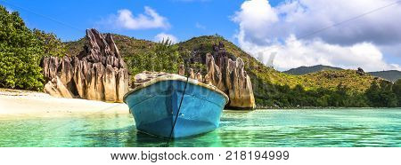 Old fishing boat on Tropical beach at Curieuse island Seychelles. Long wide banner