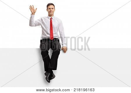 Formally dressed guy sitting on a panel and waving at the camera isolated on white background