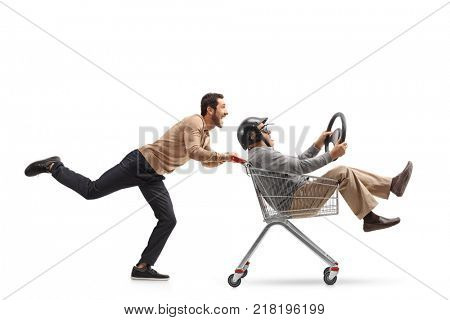 Young man pushing a shopping cart with a mature man with a helmet and a steering wheel riding inside isolated on white background